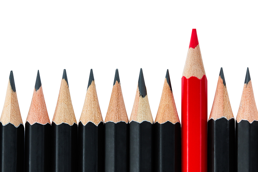 Row Of Black Pencils With One Red Pencil In Middle