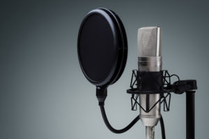 Studio microphone and pop shield on mic stand against gray backg